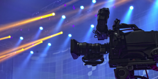 Image of video camera in foreground and a colorfully lit stage in the background.