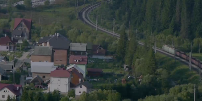 Train moving cargo past a small town near a forest.