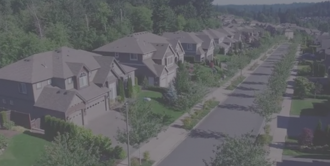 Aerial photo of a wooded subdivision of houses.