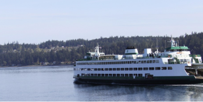 Ferry moving through calm waters with a forest in the background.