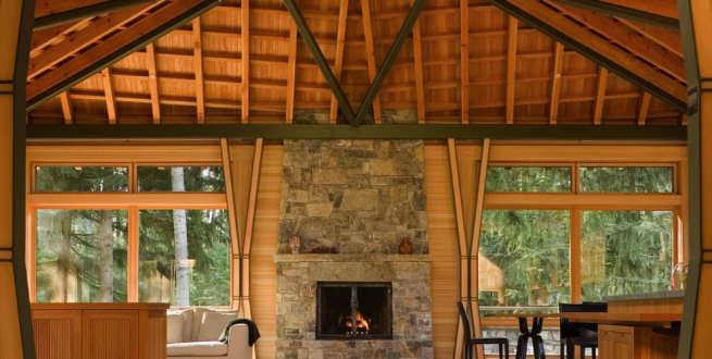 Interior photo of timber framed home with a stone fireplace.