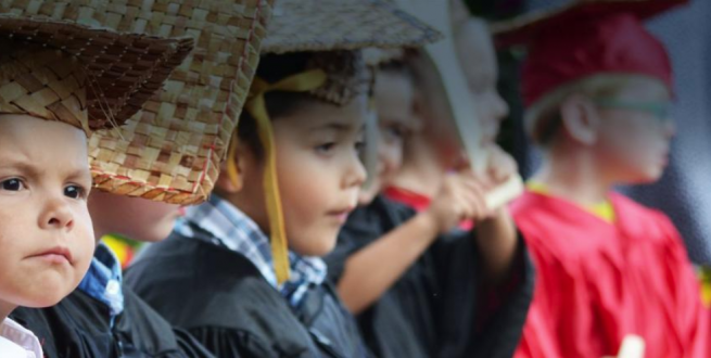 Children in a graduation ceremony wearing robes and mortar boards.