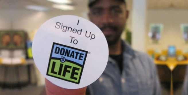 a man holding a sticker that says I signed up to donate life