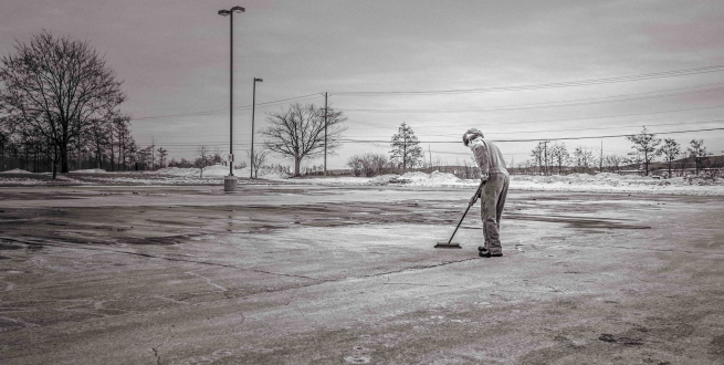 Person sweeping a parking lot