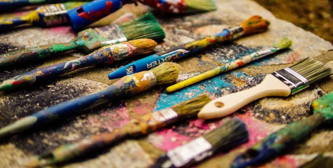 a dosen or so paint brushes on a painters table